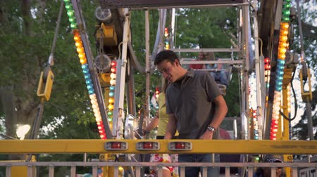 adil : A shot of two people exiting a ferris wheel ride at a carnival. The boy holds the exit door open for the girl