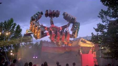 izzók : Distant shot of people flying through the air on a bright,flashing carnival ride. The machine rotates on the ground,as well as on arms that rotate in the air