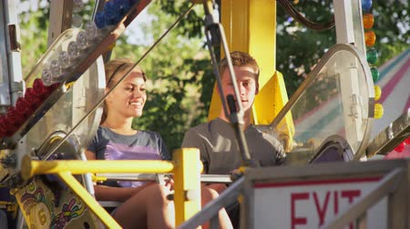 targi : Shot of a couple talking on a ferris wheel as it starts. The camera follows the couple as the wheel starts to turn