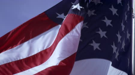 birlik : The shot is of the American flag flowing in the wind. The shot is close up so the frame is filled with the flag. The sky is seen sometimes in the background. Stok Video