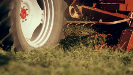 empilhamento : Close-up shot of the bottom of a hay baler as it gathers hay from the ground. The camera moves from right to left as it follow the movements of the hay baler. Stock Footage