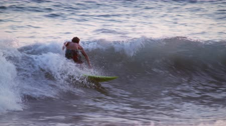 prancha de surfe : Shot of a young male surfer surfing along the coast in Costa Rica. The camera moves from left to right and back to the left as it follows the movements of the surfer. The surfer passes a group of people playing in the water.