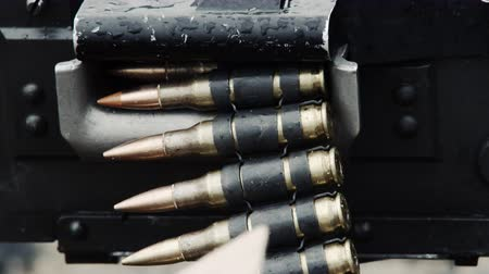 bandeja : Close-up of a chain of bullets going through a belt-fed machine gun as it is fired. Smoke comes from the gun as it is shot. From a training for Green Beret United States Army Special Forces.