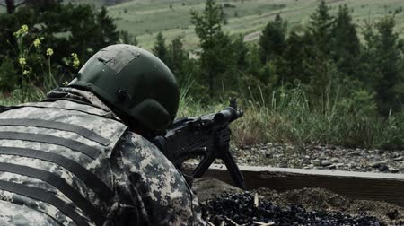 máquina : View from over the shoulder of a soldier as he is shooting a belt-fed machine gun. Trees and a distant open field are in the background. He is wearing a helmet. Puffs of smoke are given off as the gun is fired. Also seen are the casings being expelled fro