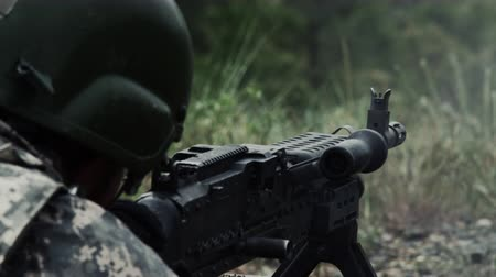 soldados : Close view over the shoulder of a soldier as he shoots a belt-fed machine gun. He is wearing a helmet. Flashes from tracer rounds can be seen occasionally. Puffs of smoke are given off as the gun is fired. Also seen are the casings being expelled from the