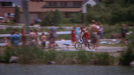 tava : A panning slow motion shot of a boy riding his bike off a dock and into a lake. The camera follows him down the path and off the ramp.