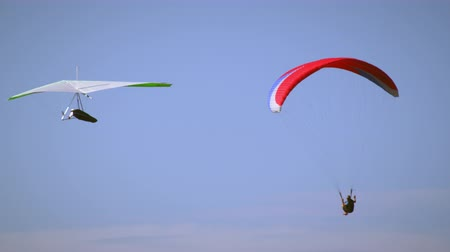 bezmotorové létání : A paraglider is flying in the air with the mountains in the distance. A hang glider quickly comes into the frame and the pair fly in the same direction near oneanother.