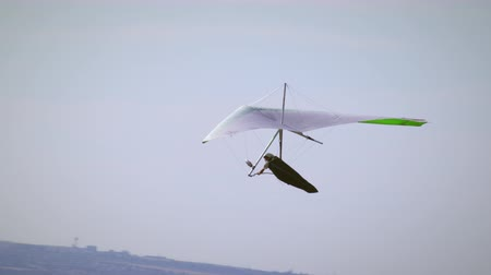 bezmotorové létání : A hang glider is seen soaring through the air. View of mountains and valley in the distance. A paraglider is seen briefly. Dostupné videozáznamy