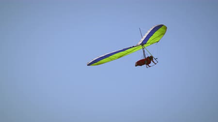 szybowiec : A lone hand glider is moving through the air to the right then turns to the left.