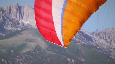 parecer : The parachutes of a two paragliders are extended while they are still standing on the ground. They seem to be testing them. Other paragliders are ready to go and people are standing around watching. A house and mountains are seen is the background.
