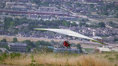 bezmotorové létání : A person on a hang glider is taking off from the side of a hill and then soars over the South Salt Lake valley in Utah. A view of the Bangerter Highway can be seen in the distance.