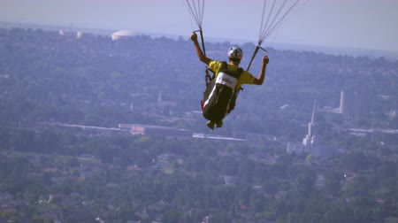 bezmotorové létání : Slow motion shot of a man paragliding over Salt Lake Valley and rising in the air until the city is no longer seen. The South Jordan LDS Temple can be seen briefly in the background. Dostupné videozáznamy