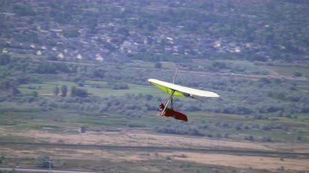 bezmotorové létání : Hang Glider is seen soaring through the air above the Jordan and South Salt Lake Valley on a clear summer day.