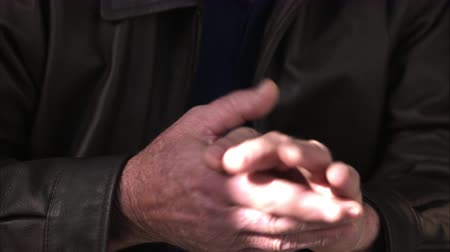 седые волосы : Up close view of man rubbing hands together.