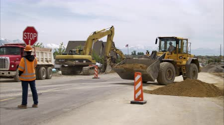 jel : Static shot of a bulldozer picking up a load of dirt and backing away as a man holding a stop sign watches.