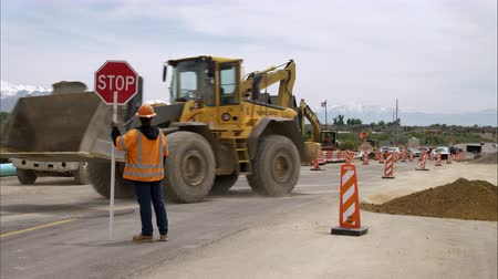 gleba : Static shot of a bulldozer picking up a load of dirt and backing away as a man holding a stop sign watches.