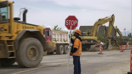 országúti : Static shot of a black highway construction crew member holding a stop sign.