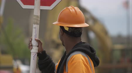 deski : Static shot of a black highway construction crew member holding a stop sign.