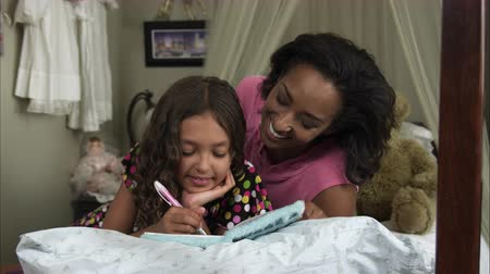 Slow motion pan of young girl writing in book as mother watches while on her bed. Stock Footage