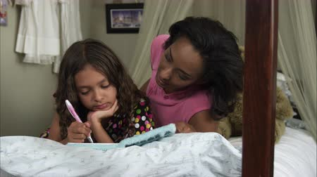 Slow motion pan of young girl writing in book as mother strokes her hair.