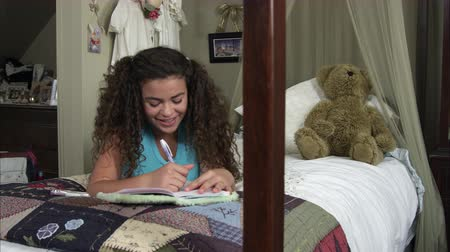czytanie : Slow motion pan of girl nodding then writting in her diary while lying on her bed.