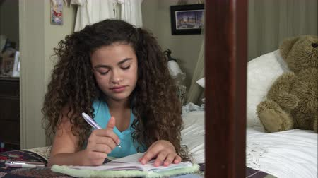 abraços : Slow motion pan of girl writing in diary then looking up to smile while lying on bed. Vídeos