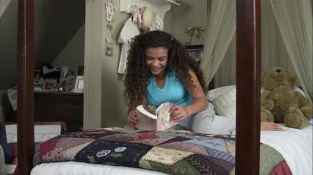 yazarak : Slow motion of girl reading book while lying across her bed.