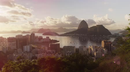 sugar loaf : Time-lapse footage with solar flares of Rio, Sugarloaf mountain, and Botafogo Bay. Cars are seen in motion as are the gentle waves of the bay. Stock Footage