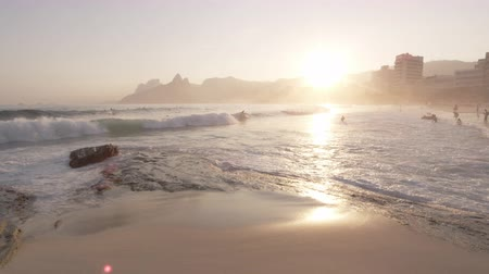 surfovat : Slow motion pan shot of waves hitting the shoreline and moving to show people swimming in the ocean. Cityscape of Rio de Janeiro, Brazil, in the background.