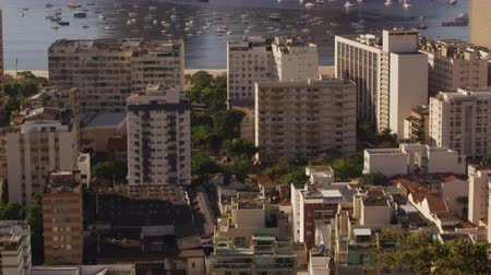 sugar loaf : Vertical tracking shot of Rio de Janeiros buildings, beach, and mountains.Trees, rooftops, sailboats, Guanabara Bay, and Sugarloaf Mountain are revealed in the video.