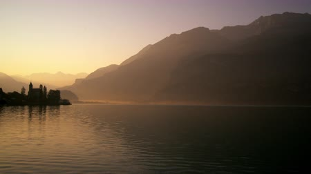 serene : Static shot of Brienz Church silhouetted against a calm brienz lake at dawn