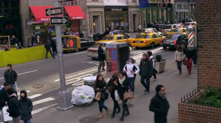 скрестив : Tracking shot of busy street. Street sign with name Bleecker is visible. People are bundled up in winter coats.