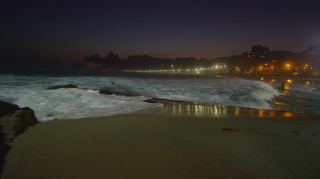 mehtap : Slow motion, pan left of a night surf on Ipanema beach with the amber glow of the city and Dois Irmos in the background Stok Video