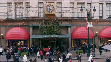odzież : Shot of Macys department store busy with shoppers. The entrance has lights and christmas tree out front. Wideo