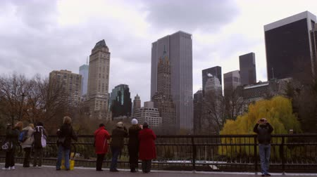 skate : Tracking shot of onlookers at ice rink. Cityscape is visible in the background. Stock Footage