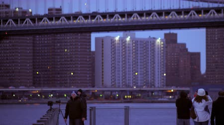 télen : Panning shot of tourists taking pictures and videos of the Brooklyn bridge in New york City. The shot starts off as a view of the bridge itself and then pans down to the tourists.