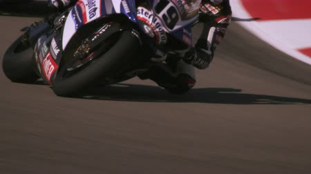 lovas : Slow motion shot of a motorcycle racer maneuvering at a curve on a race track