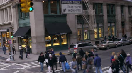 útkereszteződés : Dolly shot of people crossing an intersection in New York City. There are several pedestrians crossing as the car drives by.