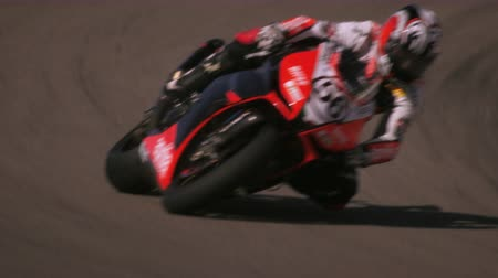 motorsports : Slow motion footage of motorcycle racers on the race circuit. The videographer shows the race participants and tracks racer no. 56. Stock Footage