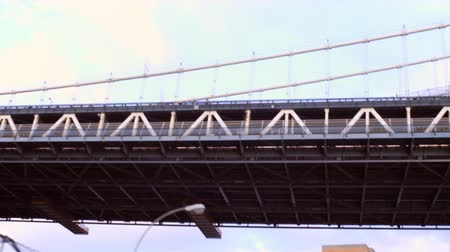 télen : Dolly shot going under a bridge in New York City. The camera angle is from a car looking up at the bridge as it drives under. Stock mozgókép