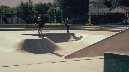 patenci : Shot of two skateboarders jumoing in and out of skatepark transition. The person to the right jumps out of the ramp, and the person to the left ollies into the ramp.