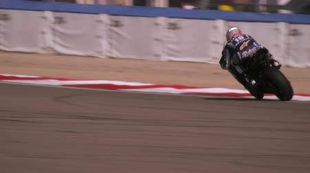 motorsports : Shot of a motorcycle racer turning at a curve and coming very close to the concrete barrier Stock Footage