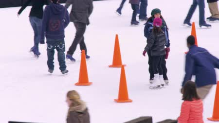 unbalanced : Slow motion panning shot of ice skaters on the Central Park ice rink. Filmed in New York City New York.