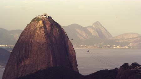 kabely : Static shot of cable cars traveling back and forth from Sugarloaf mountain in Rio De Janeiro, more brightly lit