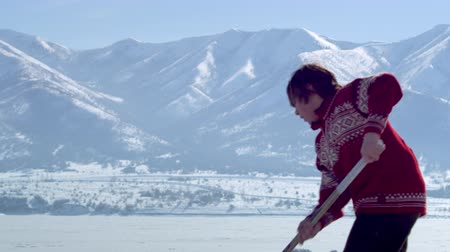 atleta : A close up shot of a boy dribbling a hockey puck up and down an ice rink surrounded by snow capped mountains. Half of the shots focus on the stick and the puck and the other half on the upper half of the boys body