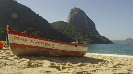 geological feature : Static shot of a single fishing skiff painted with Praia Vermelha I at Rio with Sugarloaf Mountain in the distance. Filmed June 19, 2013. Stock Footage