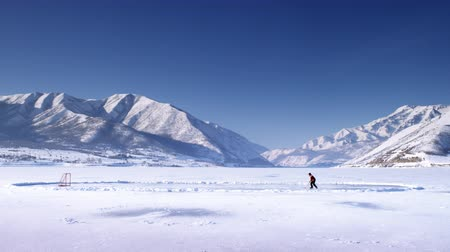 patim : A distant scenic shot of an iced over pond surrounded by snow covered mountains and the sun glistening over the top. A person dribbles a hockey puck across the lake towards the net