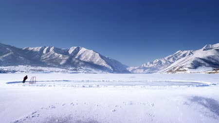 skate : A distant scenic shot of an iced over pond surrounded by snow covered mountains and the sun glistening over the top. A person dribbles a hockey puck across the lake towards the net