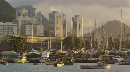 gloria : Static shot of Marina da Gloria at sunset with many boats docked in the marina in the shadowsof buildings and mountains. Filmed June 19, 2013. Stock Footage