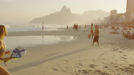 brasileiro : Slow motion, 180 tracking shot of a couple playing tennis on Ipanema beach at dusk against the backdrop of Dois Irmos and Rio condos. Stock Footage